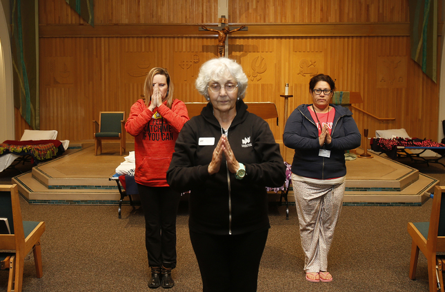 "Michell Waters, 41, left, follows instructor and volunteer Mary Ann Smith, center,  and Irene Lopez, 41, practice meditation at Holy Spirit Church in San Jose, Calif., on Thursday, Jan. 28, 2016. Three San Jose churches that will shelter, feed and help homeless women rebuild their lives over three months. All of them are ""medically fragile"" women selected by Catholic Charities. (Josie Lepe/Bay Area News Group)"